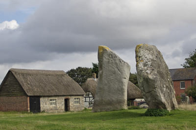 two huge prehistoric standing stones in front of a thatched building