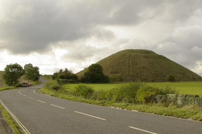large conical hill towering behind a winding main road